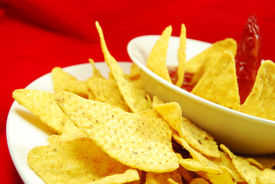stock photo of doritos  - Plate of chips (nachos) and hot salsa dip sauce ** Note: Shallow depth of field ** Note: Slight graininess, best at smaller sizes - JPG