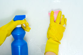 stock photo of house cleaning  - The woman is engaged in cleaning in the house and washes a wall - JPG