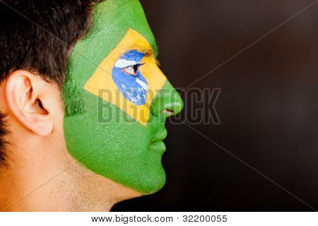 Profile view of a Brazilian man with flag painted on his face