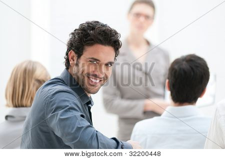 Satisfied businessman looking at camera during a business conference