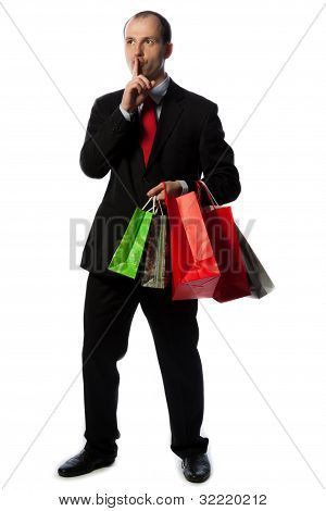 Man In Suit With Shopping Bags And Making Quiet Sign With Hand