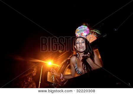 Young Woman sitting in truck at night with Birthday Balloons