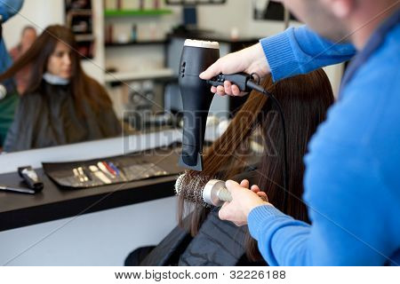 Hairdresser Drying Woman's Hair Using Hair Dryer And Round Brush. Selective Focus.