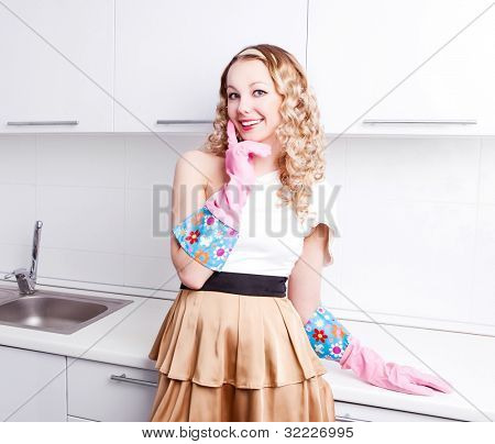 beautiful young housewife wearing rubber gloves in the kitchen at home