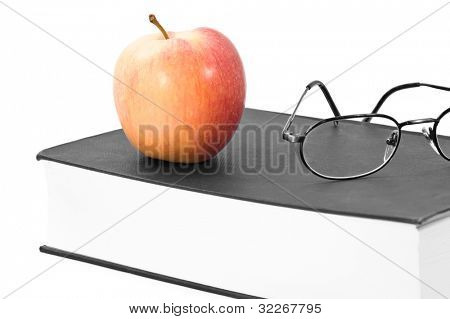 Glasses and book in black and white, only apple in color