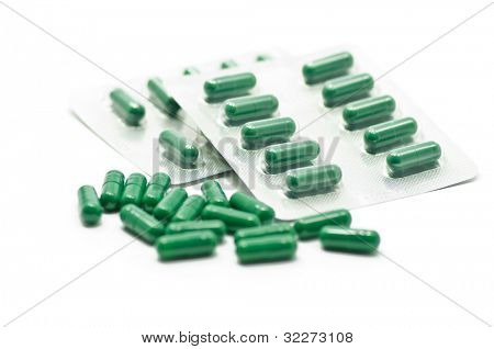 Close up on green pills on white background