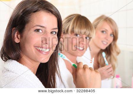 Three female house mates brushing their teeth