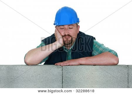 Tired builder resting against wall