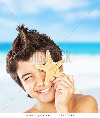 Happy face cute boy with starfish on the beach, closeup portrait of preteen brunette child, male kid model having fun outdoor, summer travel and beach vacation