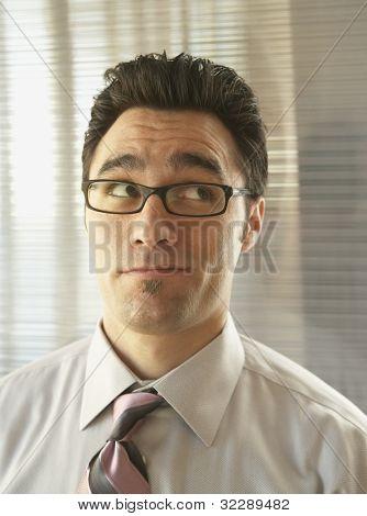Skeptical businessman rolling his eyes