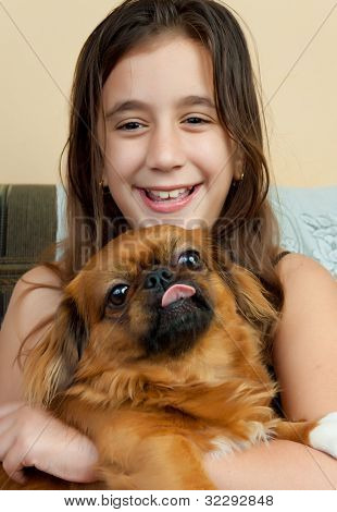 Beautiful hispanic girl carrying her small pekingese dog and smiling