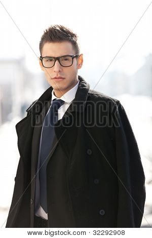 Businessman wearing suit , coat and glasses, looking to the camera - outdoor picture