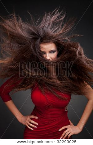 Young woman with hair flying  on dark background