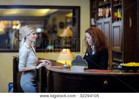 business woman  at the reception of a hotel checking in