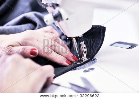 woman Hands of Seamstress Using Sewing Machine tailor and new clothes fahion reparation concept