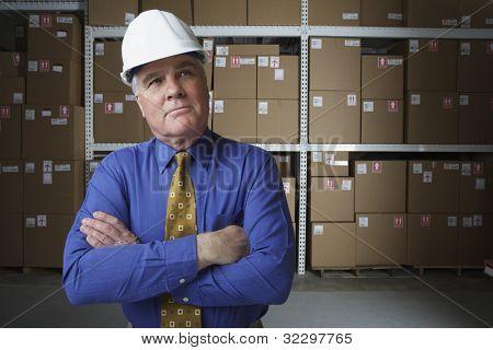Businessman wearing hard hat in warehouse