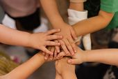 Childrens Hands Piled On Top Of Each Other. Childrens Team And Team Building Among The Little Guys. poster