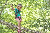 Little Girl Climbing In Adventure Park. Boy Enjoys Climbing In The Ropes Course Adventure. poster
