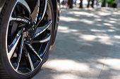 The Front Of The Sports Car. Wheel Of A Sports Car On The Background Of A Blurred Sidewalk In A Tren poster