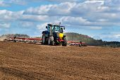 A Blue Tractor Sows Grain. Farm Work On A Farm In The Czech Republic. Tractor On A Wheat Field. Agri poster