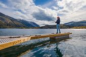 Woman fishing on Fishing rod spinning in Norway. Fishing in Norway is a way to embrace the local lif poster