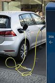 Charging The Electric Car Silver Color. Power Supply For Electric Vehicle Charging. Close Up Of The  poster