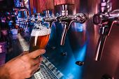 Hand Of Bartender Pouring A Large Lager Beer In Tap. Bright And Modern Neon Light, Males Hands. Pour poster
