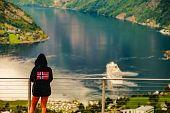 Tourist Wearing Norwegian Flag Clothing Enjoying Scenic View Over Fjord Geirangerfjorden From Flydal poster