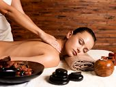 Beautiful woman with closed eyes having massage of body in the spa salon. Beauty treatment concept. poster