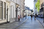 Street With Historical Buildings And Motion Blur Pedestrians In Breda In The Netherlands poster