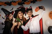 Group of young adult and teenager people celebrating a Halloween party carnival Festival in Hallowee poster