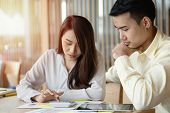 Unhappy Asian Couples Are Calculating Income And Expenses To Cut Unnecessary Expenses. Concepts For  poster