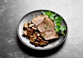 Slow Cooked Beef With Mushrooms On Dark Stone Background. Tasty Stewed Meat With Mushrooms. Close Up poster