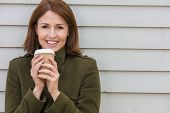 Portrait shot of an attractive, successful and happy single middle aged woman female outside drinkin poster
