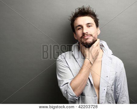 Porträt eines jungen Mannes nimmt sich für eine Kehle (Studio)