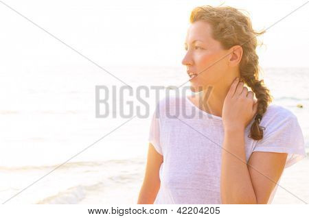 young woman on beach at sunrise