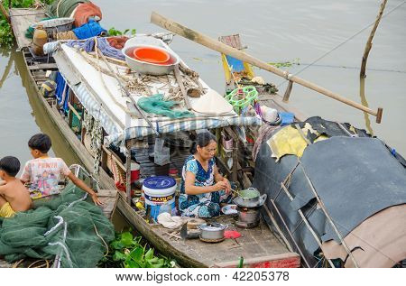 CHAU DOC, VIETNAM - JANUARY 2: Unidentified fisherman's wife cooks a meal on her wooden boat while her children are resting near her on January 2, 2013, in Chau Doc , Vietnam.