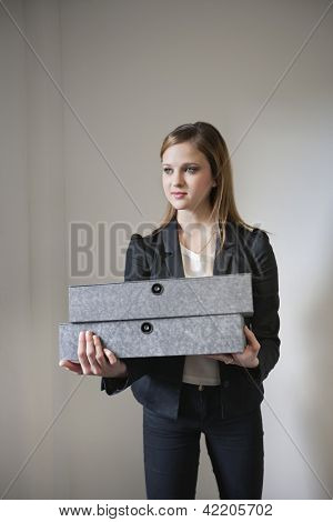 Young businesswoman holding box file