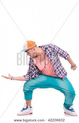 cool male dancer holding his palm out and looking at it, with elbow on knee, over white background