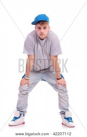modern young dancer posing with hands on knees is looking at the camera with a serious look on his face, on white background