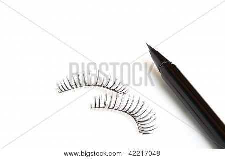 False Eyelashes And Eyeliner On White Background