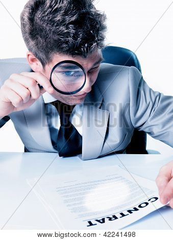 Businessman With Magnifying Glass Reading The Fineprint In A Contract