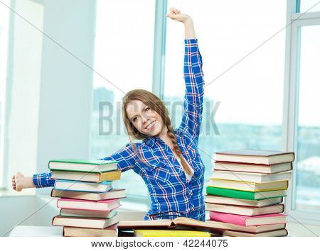 Portrait of diligent student relaxing during studies with book stacks in front