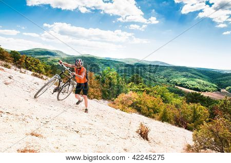 female cyclist raises his mountain bike on the mountain