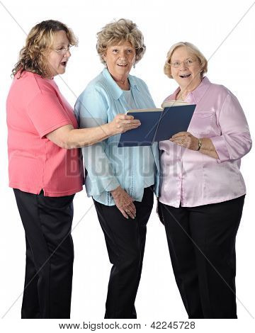 Three senior women singing together from a songbook.  On a white background.