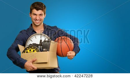 Happy Young Man Holding Cardboxes Gesturing On Blue Background