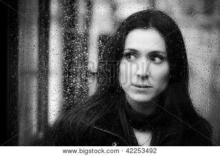 Young woman peeking behind waterdropped glass