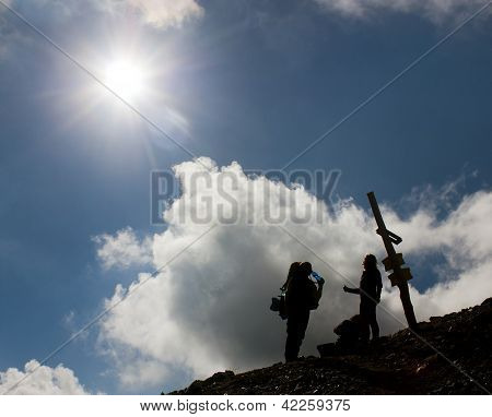 silhouettes of tourists on mountains with sun and beautiful sky
