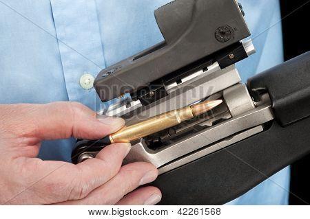 A businessman wearing a dress shirt loads an assault rifle with a single 223 bullet