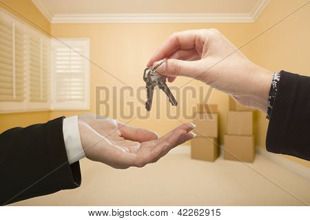 Woman Handing Over the House Keys To A New Home Inside Empty Room.